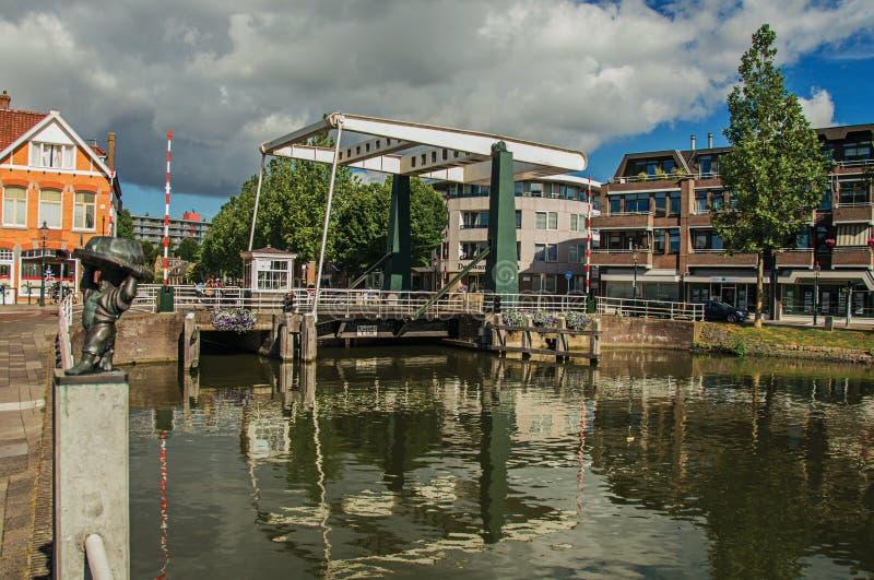 Les Chambres et le pont en bascule se sont reflétés dans la surface large de l'eau de canal sur le coucher du soleil dans Weesp images stock
