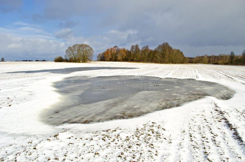 Les champs d'extrémité d'hiver avec de l'eau la neige et grand inondent le magma image stock