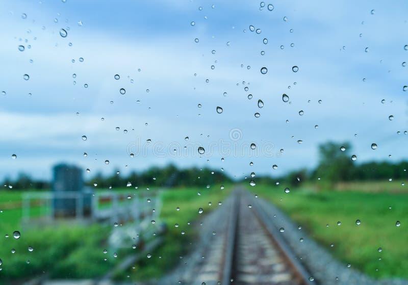 Les champs verts et les voies ferrées après pluie derrière la fenêtre, semblent frais, détendent, calment et apaisent photographie stock