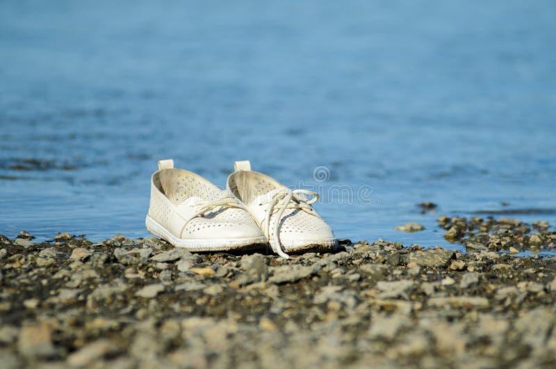 Les chaussures blanches ont laissé le bord de la mer image stock