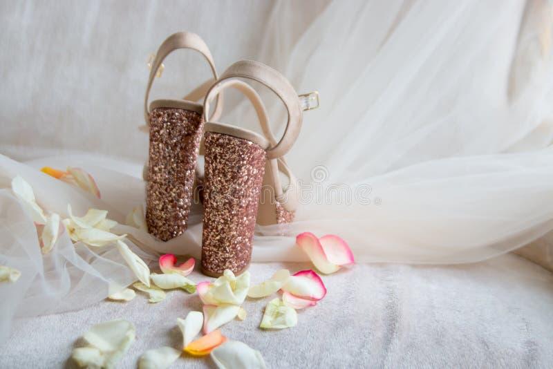 les chaussures brillantes d'or sur Tulle léger dans des pétales de rose soutiennent photographie stock libre de droits