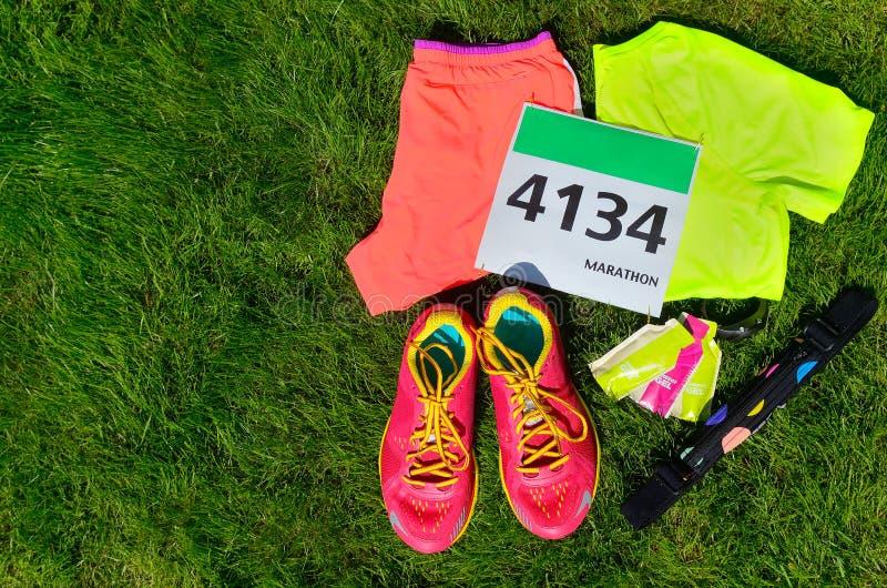 Les chaussures de course, bavoir de course de marathon (nombre), coureurs embrayent et des gels d'énergie sur le fond d'herbe images libres de droits