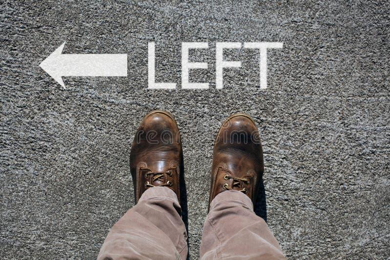 Les chaussures de l'homme regardent de la gauche ci-dessus, de mot et d'une flèche indiquant les directions avec l'espace cpy pou images libres de droits