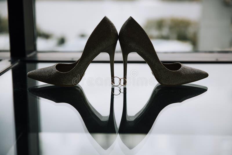 Les chaussures de la jeune mariée et les anneaux de mariage images libres de droits