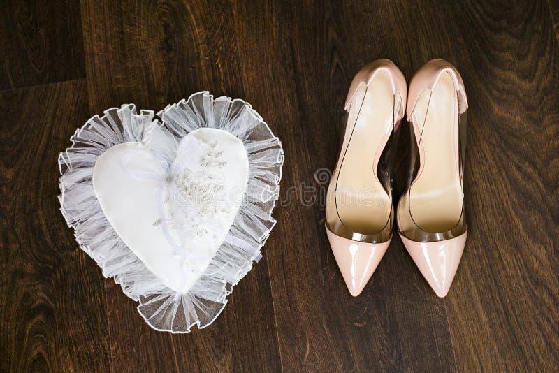 Les chaussures de mariage beige et les anneaux de mariage nuptiales d'or sur le blanc décorent l'oreiller photos libres de droits