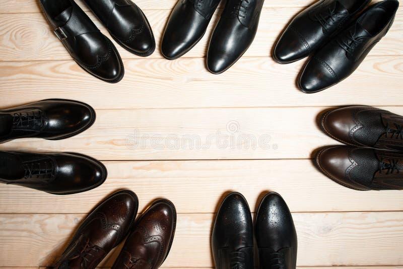 Les chaussures des différents hommes en cuir sur le fond en bois photos stock