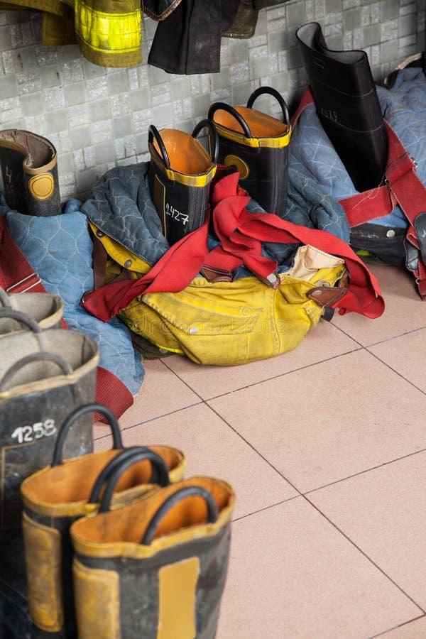 Les chaussures du sapeur-pompier sur le plancher à la caserne de pompiers photos stock