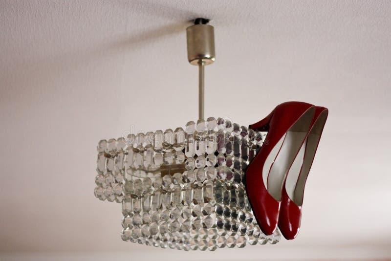 Les chaussures en cuir rouges avec des talons hauts accrochent sur un lustre en cristal sur le plafond photo libre de droits
