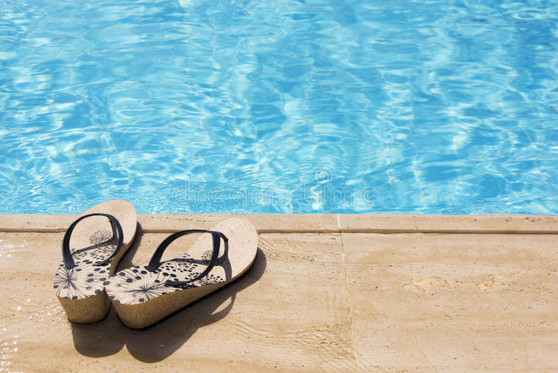 Les chaussures est au bord de la piscine photo libre de droits