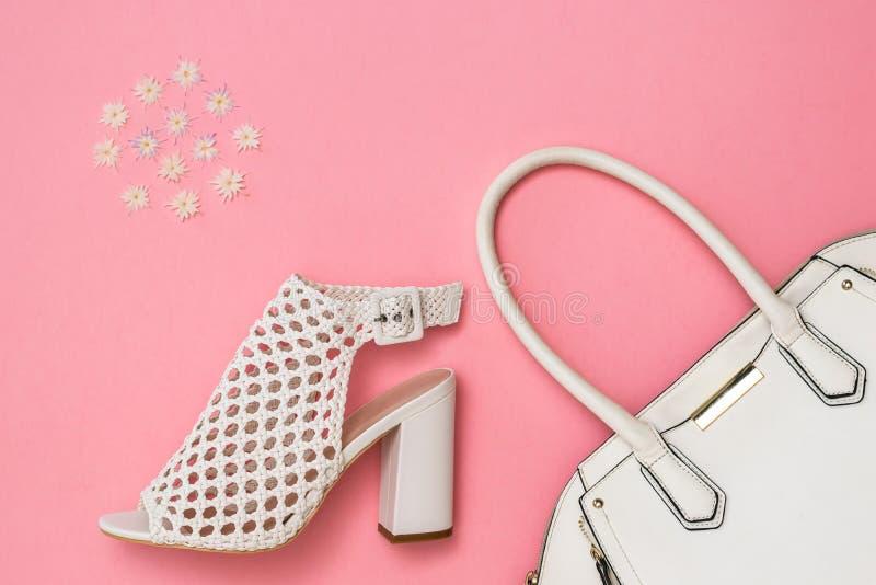 Les chaussures, le sac blanc et le modèle de femmes blanches de couleur sur le fond rose Configuration plate photo libre de droits