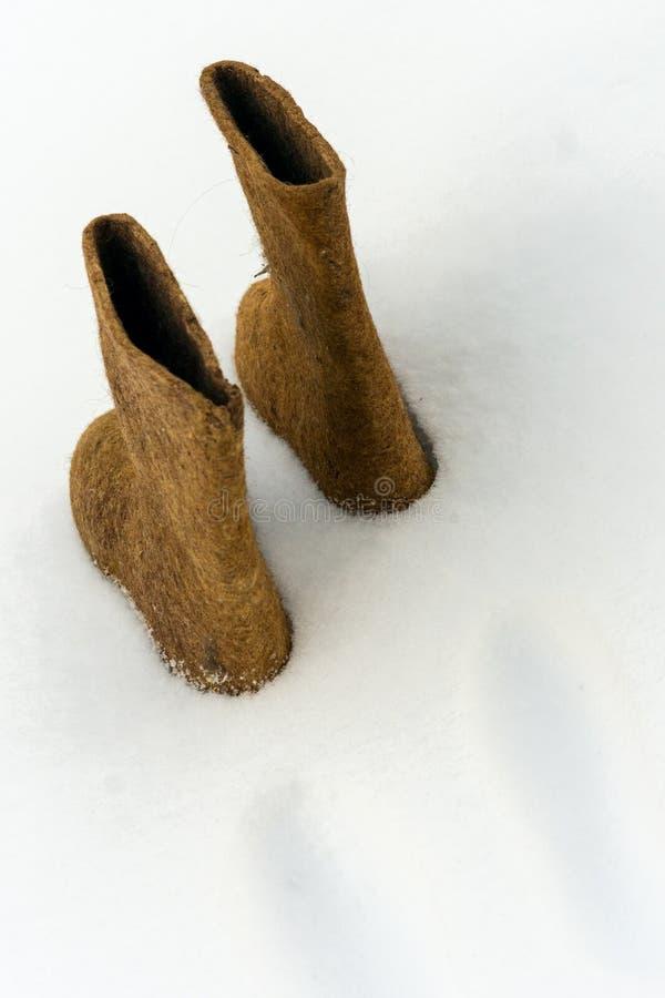 Les chaussures traditionnelles d'hiver ont senti des bottes sur la neige blanche photos stock