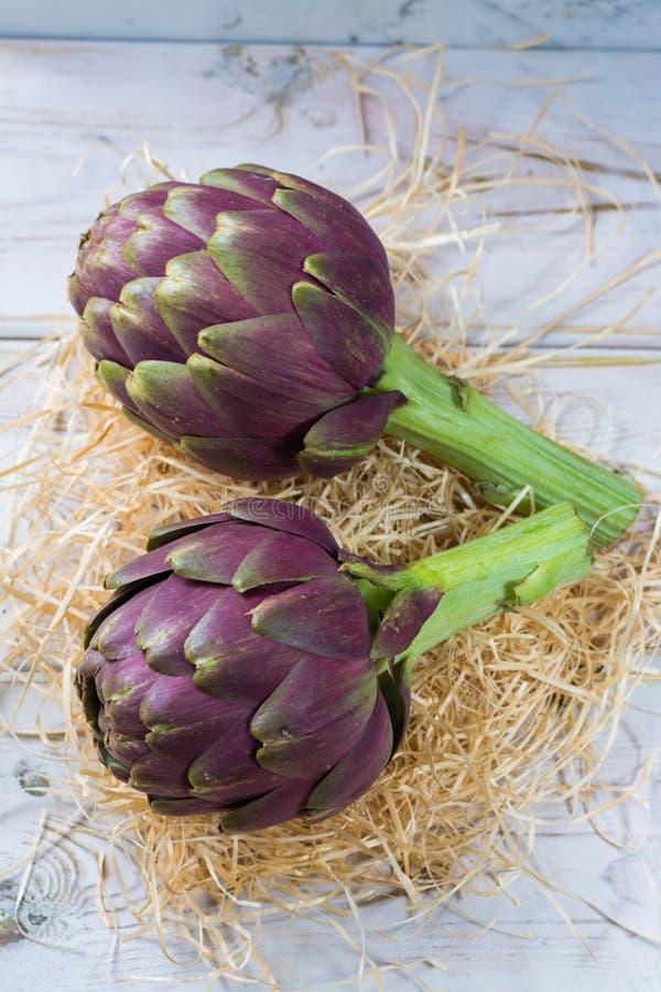 Les chefs de fleur vert-pourpres de grands artichauts frais de Romanesco préparent t image stock