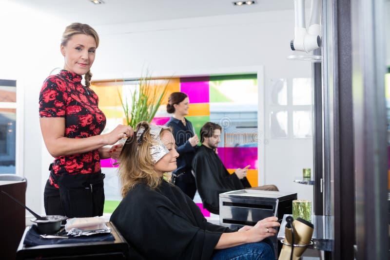 Les cheveux de Highlighting Customer de coiffeur dans le salon photos stock