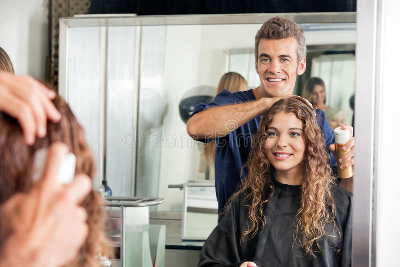 Les cheveux du client d'arrangement de styliste en coiffure tout en regardant photographie stock