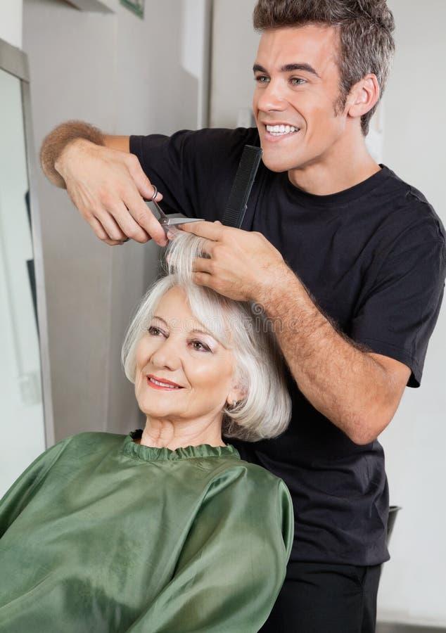Les cheveux du client de coupe de styliste en coiffure dans le salon images stock