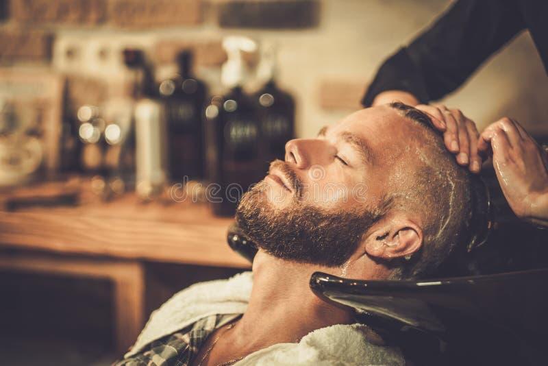 Les cheveux du client de lavage de styliste en coiffure images libres de droits