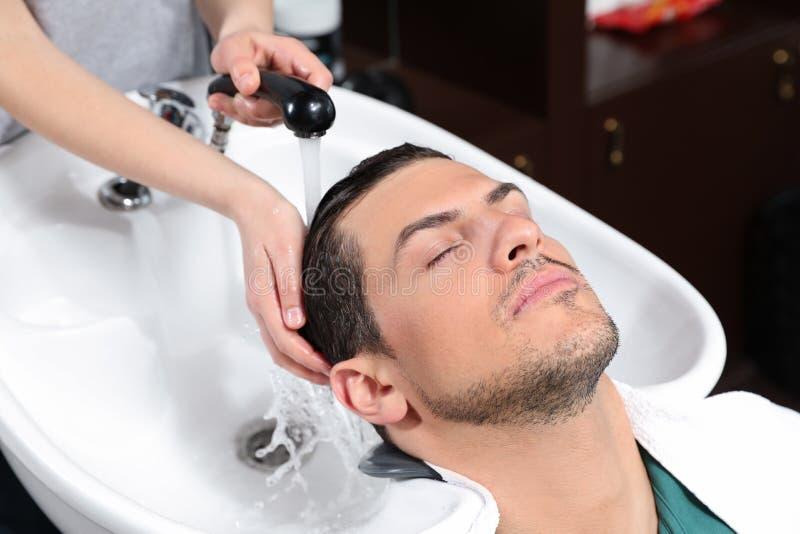 Les cheveux du client de lavage de styliste à l'évier photo libre de droits