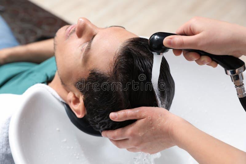 Les cheveux du client de lavage de styliste à l'évier photographie stock libre de droits