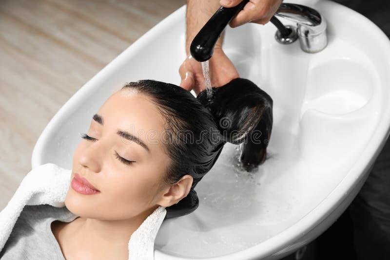 Les cheveux du client de lavage de styliste à l'évier images stock