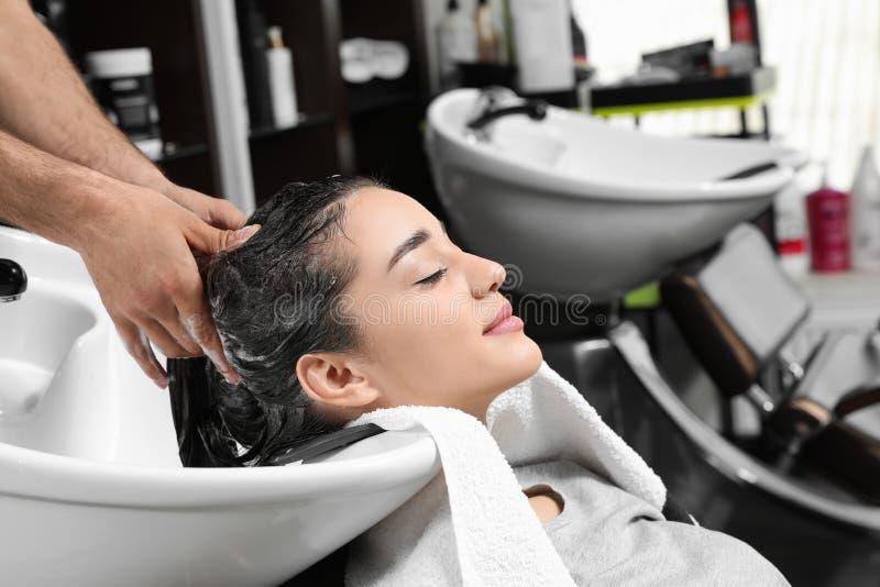 Les cheveux du client de lavage de styliste à l'évier dans le salon photographie stock