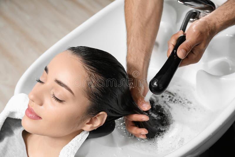 Les cheveux du client de lavage de styliste à l'évier photo stock