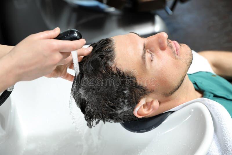 Les cheveux du client de lavage de styliste à l'évier images libres de droits