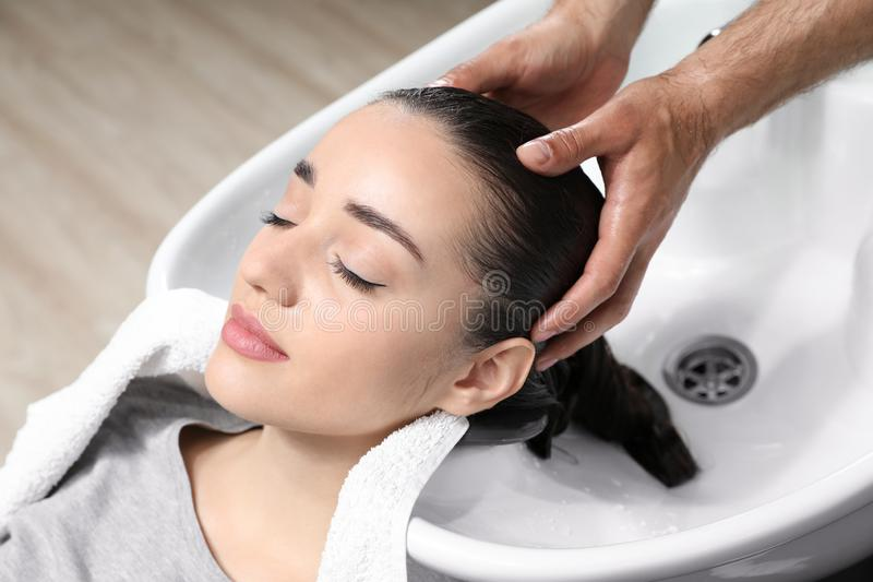Les cheveux du client de lavage de styliste à l'évier photos stock