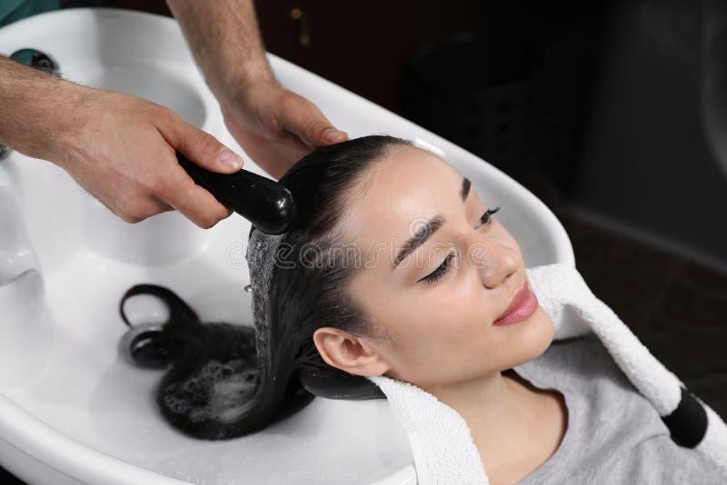 Les cheveux du client de lavage de styliste à l'évier dans le salon images libres de droits