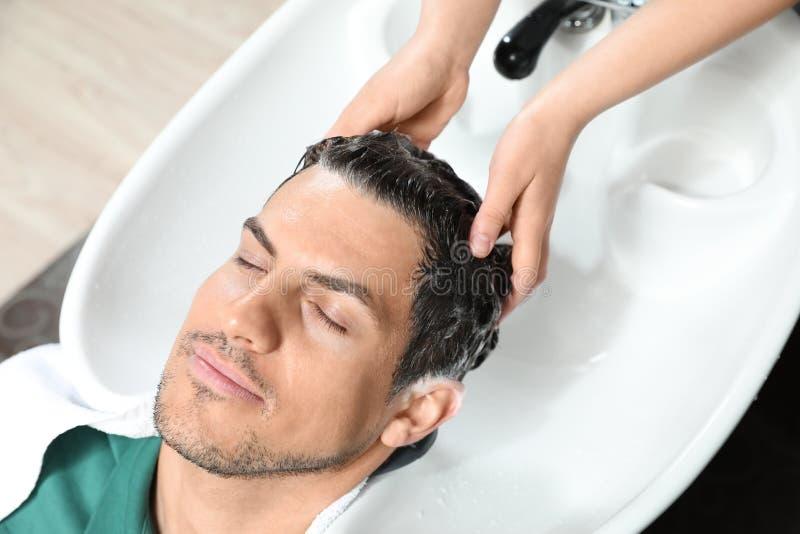 Les cheveux du client de lavage de styliste à l'évier photographie stock