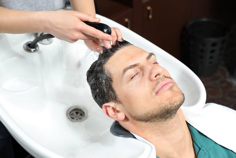 Les cheveux du client de lavage de styliste à l'évier dans le salon photographie stock libre de droits