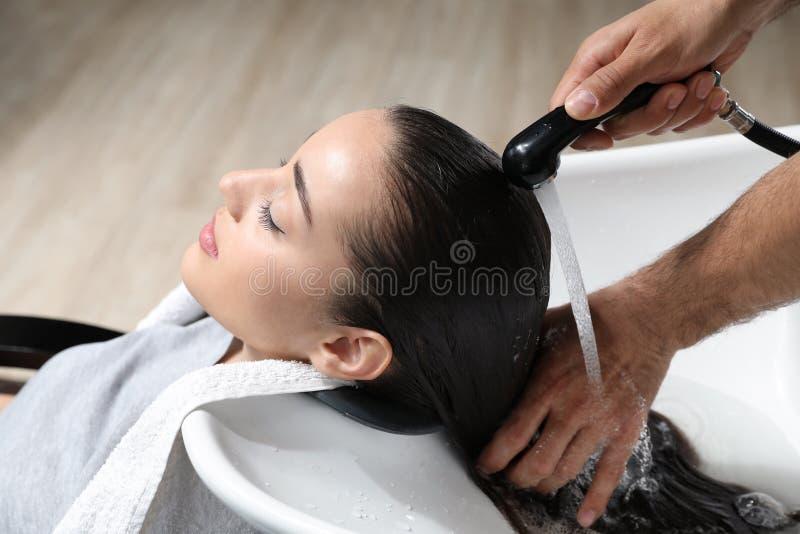Les cheveux du client de lavage de styliste à l'évier image libre de droits
