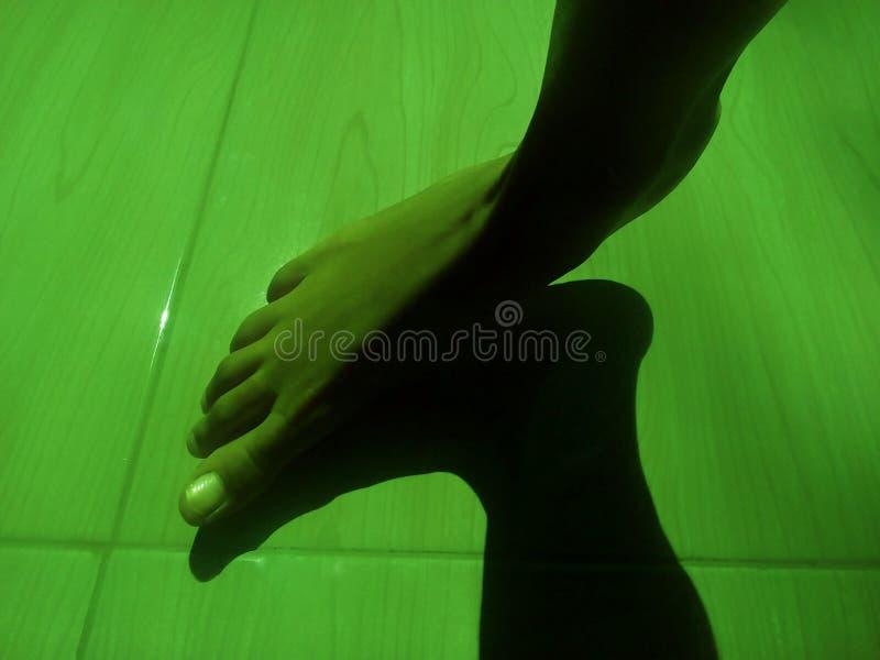 Les chevilles des enfants et l'ombre noire sur un sol vert photo libre de droits