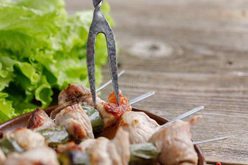 Les chiches-kebabs sensibles de porc cuits sur un feu ouvert avec une fourchette exquise ont collé dans eux la vie toujours sur u photographie stock