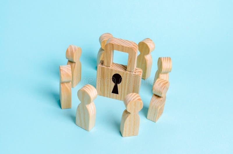 Les chiffres en bois des personnes se tiennent autour d'un cadenas Le concept de la sécurité et de la sécurité, la protection des photographie stock
