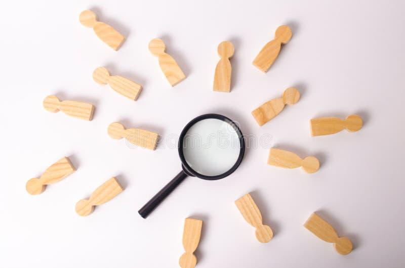 Les chiffres en bois des personnes se trouvent autour d'une loupe sur un fond blanc Le concept de la recherche des personnes et d images stock
