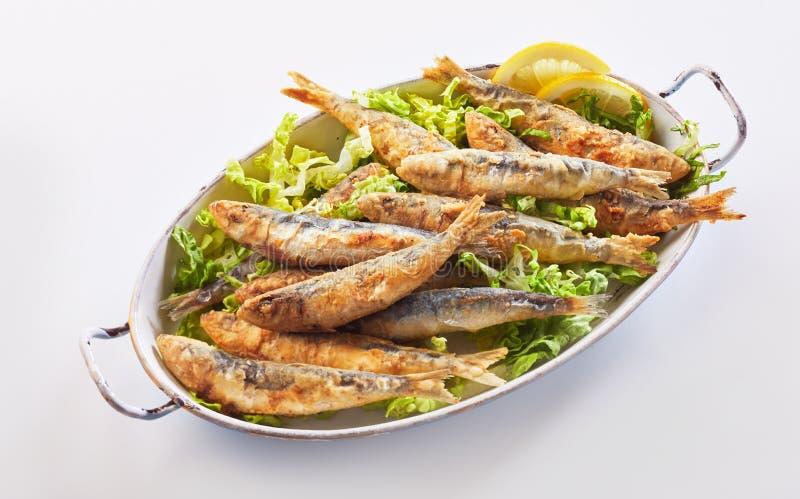 Les chips ont fait frire des sardines dans la pâte lisse sur la laitue fraîche photographie stock libre de droits