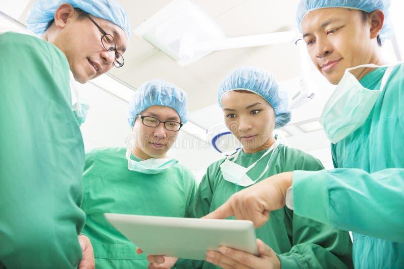 Les chirurgiens à l'aide du comprimé pour discuter le mode opératoire photo libre de droits