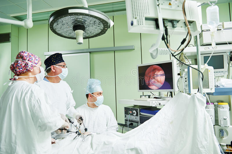 Les chirurgiens team des mains pendant l'opération abdominale laparoscopic dans la chirurgie d'enfant images stock
