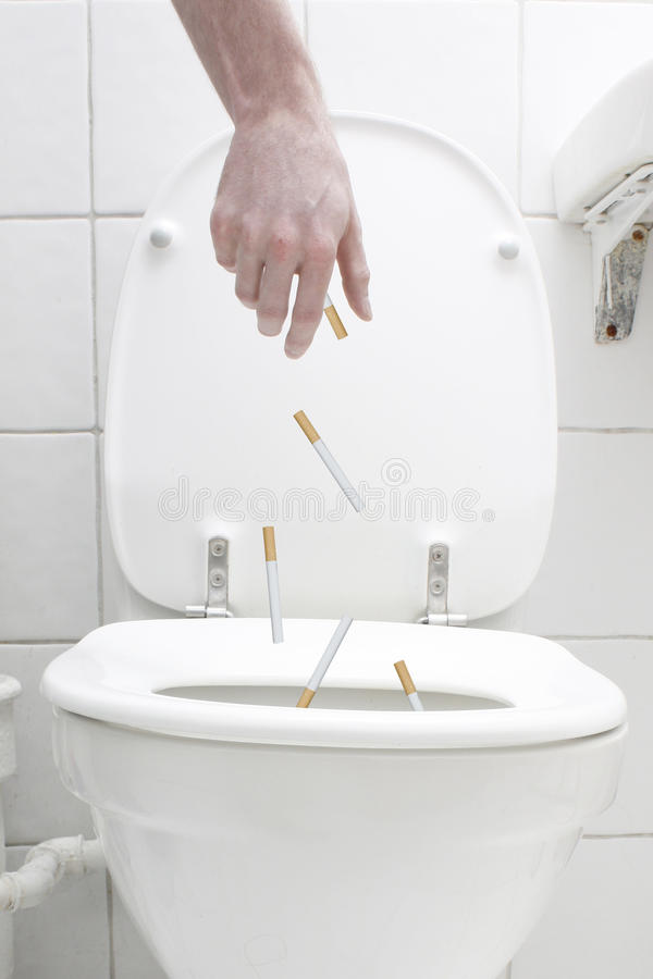 Les cigarettes avalent la toilette photographie stock