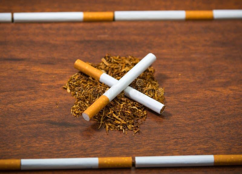 Les cigarettes se trouvant sur la surface en bois formant dans les lignes croisées, tabac ont écarté autour, vu d'en haut photo stock