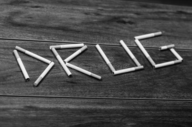 Les cigarettes se trouvant sur la surface en bois ont formé dans la drogue de mot, concept contre le tabac artistique, édition no image libre de droits