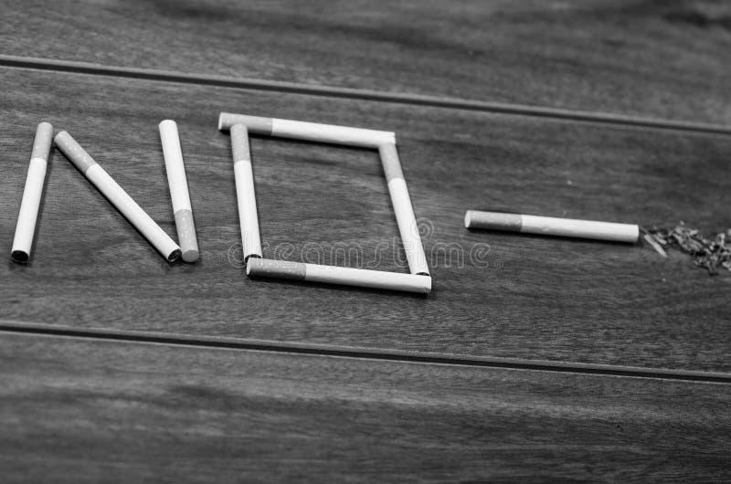 Les cigarettes se trouvant sur la surface en bois ont formé dans le mot aucun, concept contre le tabac artistique, édition noire  image libre de droits