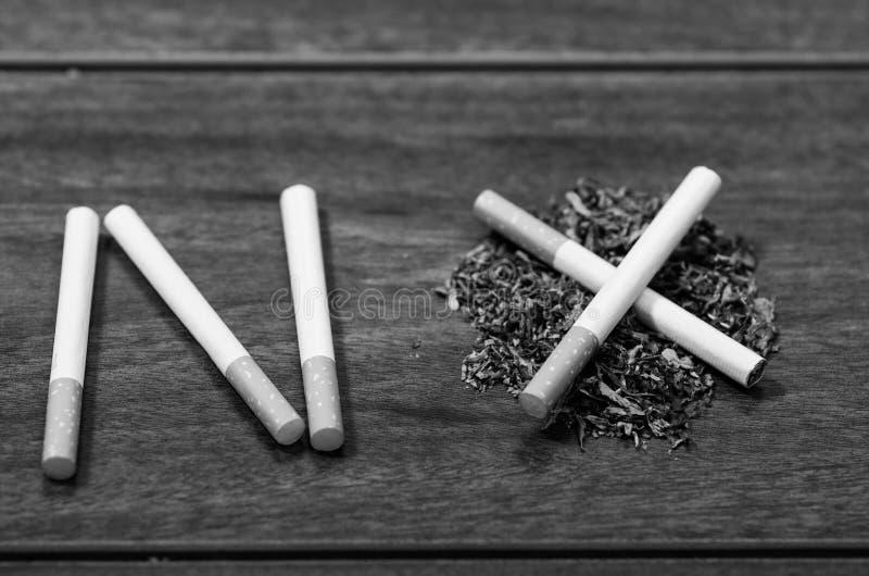 Les cigarettes se trouvant sur la surface en bois ont formé dans le mot aucun, concept contre le tabac artistique, édition noire  images stock