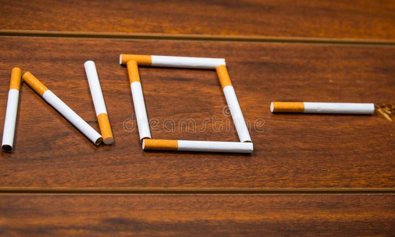 Les cigarettes se trouvant sur la surface en bois ont formé dans le mot aucun, concept contre le tabac artistique photographie stock