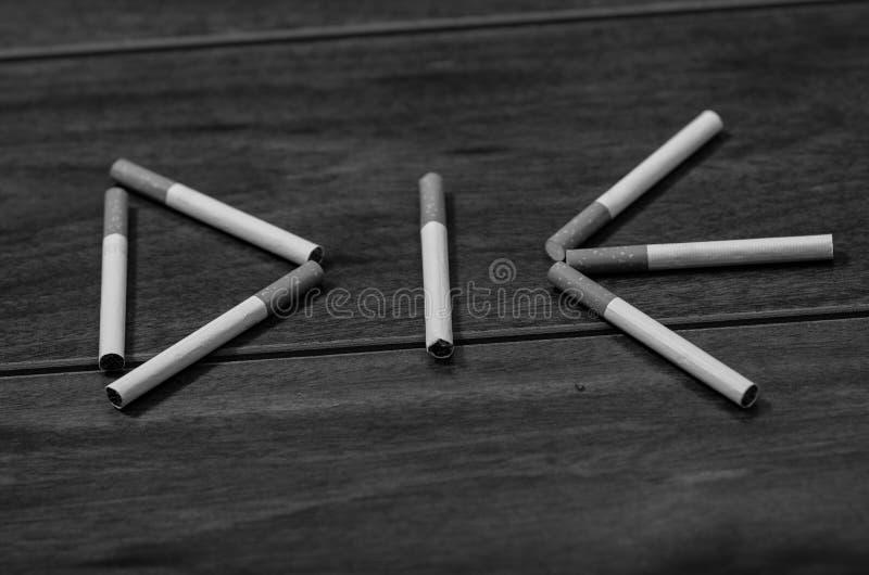Les cigarettes se trouvant sur la surface en bois ont formé dans le mot meurent, concept contre le tabac artistique, édition noir photo libre de droits