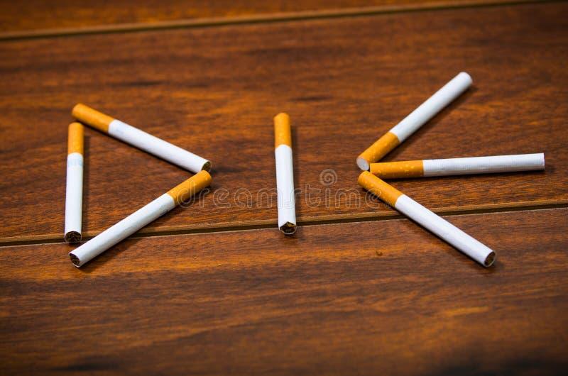 Les cigarettes se trouvant sur la surface en bois ont formé dans le mot meurent, concept contre le tabac artistique photos libres de droits
