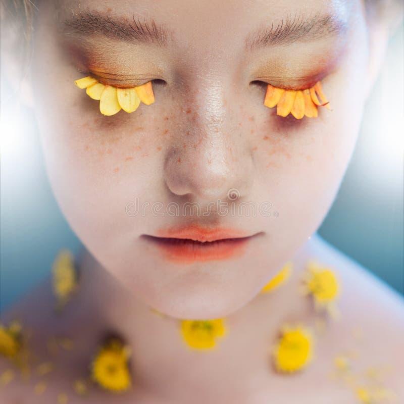 Les cils aiment des pétales des fleurs Belle jeune fille dans l'image de la flore, portrait en gros plan photos stock