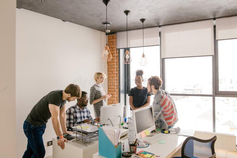 Les cinq jeunes se tiennent dans le bureau et font le plan du fonctionnement images libres de droits