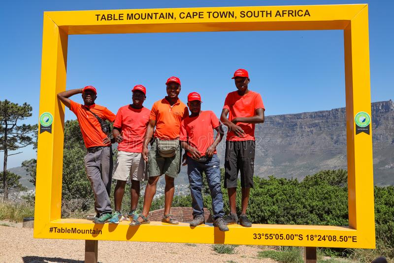 Les cinq types de sourire en rouge prendre une photo dans le grand cadre jaune sur la colline de signal à Cape Town avec la mont photographie stock libre de droits