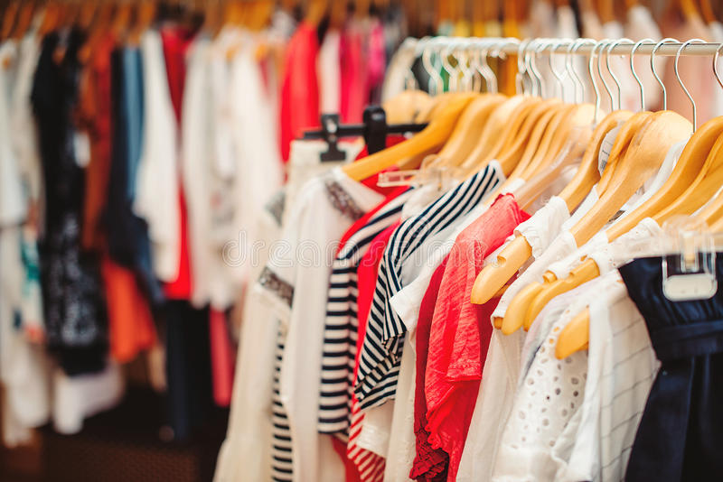 Les cintres avec les vêtements colorés dans des femmes font des emplettes Vente d'été image stock